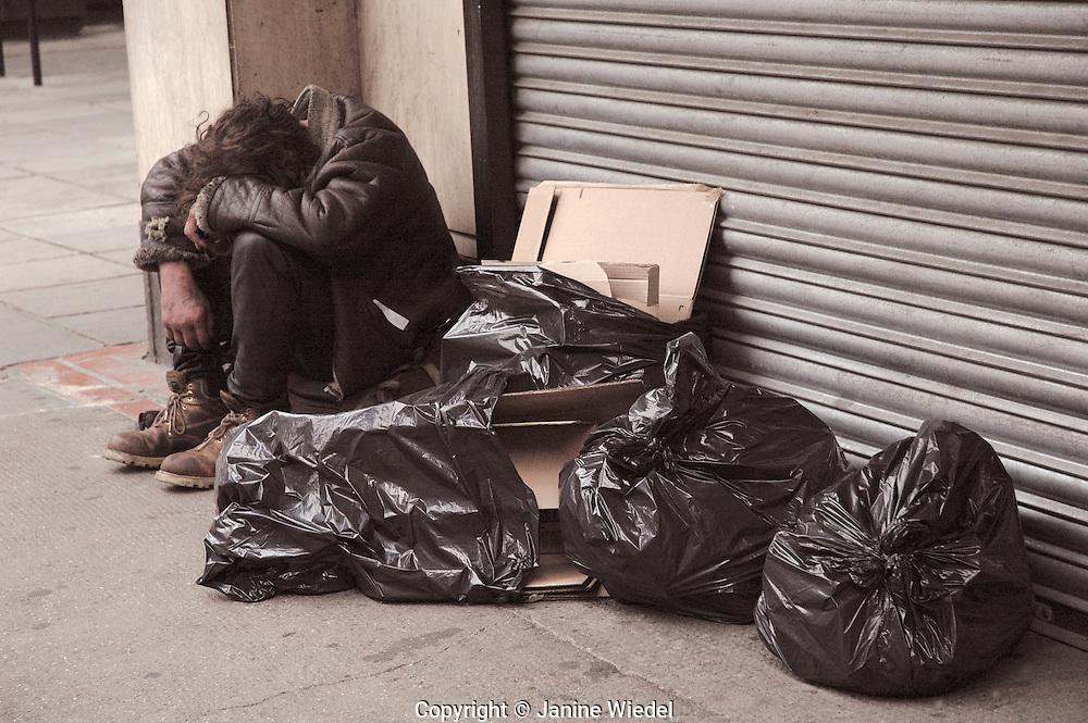homeless man asleep next to garbage sack in London street