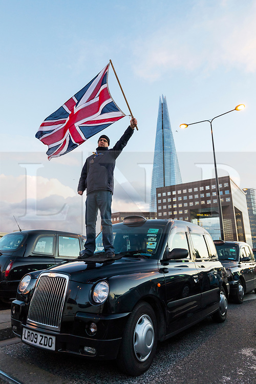© Licensed to London News Pictures. 18/01/2018. London, UK. A Black Cab driver waves the Union Jack on the bonnet of a taxi during a blockade of London Bridge to protest against minicab firm Uber's continued operation in London. Transport for London revoked Uber's license in September 2017 but the decision is currently under appeal. Photo credit: Rob Pinney/LNP