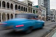 A vintage car speeds down the Malecon. Habana, Cuba.