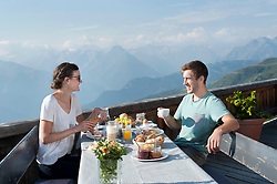 Young couple eating breakfast on terrace and smiling, Zillertal, Tyrol, Austria