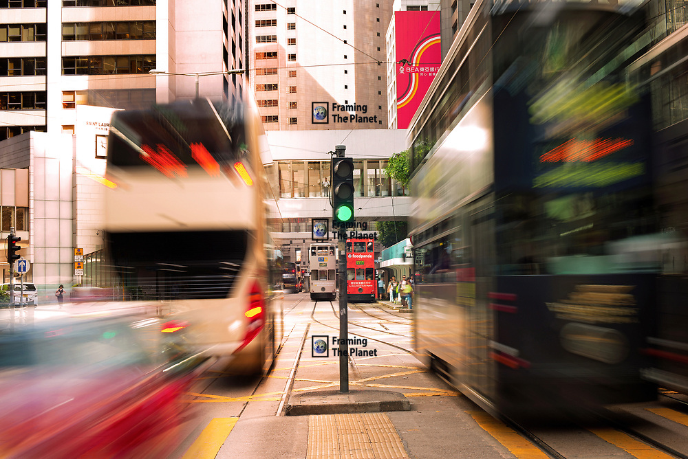 This shot was taken from a busy junction right in the heart of Hong Kong's Central district. The buses, taxis and trams rush past through the over crowded streets and rush hour.<br /> <br /> Available to download for personal and commercial use or to purchase as a canvas print, photo print and framed photo print.