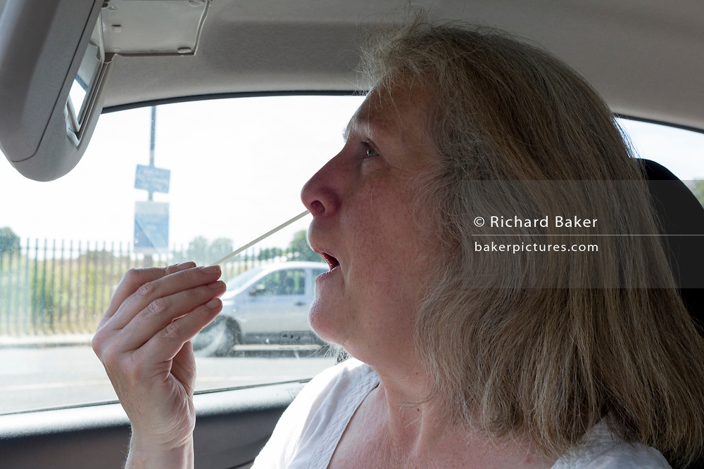 A middle-aged lady pushes a swab up her nose from the driver's seat of her car during a self-administered Coronavirus (COVID-19) test in south London. There are four steps to the self-administered Covid-19 test (inserting a swab into the nose and throat) which the public works through in their car, windows up and all communications with army personnel via phone, in a south London leisure centre, on 2nd June 2020, in London, England. The kit provided consists of a booklet, plastic bag, swab, vial, bar codes and a sealable biohazard bag. The swab sample is taken from the back of the throat and nasal passage with the contents sealed and returned to soldiers through a narrow window. The whole process takes between 5-10mins with results available with 48hrs.