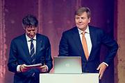 Koning Willem Alexande op de Nationale Vrijwilligersdag, de jubileumbijeenkomst van het Oranje Fonds in de Fabrique in Maarssen. Tijdens de bijeenkomst 'Morgen is Vandaag' staan, naast een terugblik op afgelopen 15 jaar, de ontwikkelingen van het Oranje Fonds voor de komende jaren centraal.<br /> <br /> King Willem Alexande on the National Volunteer Day, the jubilee meeting of the Oranje Fonds in the Fabrique in Maarssen. During the 'Tomorrow is Today' meeting, in addition to a review of the past 15 years, the developments of the Oranje Fonds will be central for the coming years.<br /> <br /> Op de foto / On the photo:  De heer Douwes nodigt de Koning op het podium uit om een interactieve landkaart  te onthullen / Mr. Douwes invites the King to the stage to reveal an interactive map