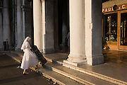 Nun manhandles case up steps in Piazza San Marco, Venice, Italy.