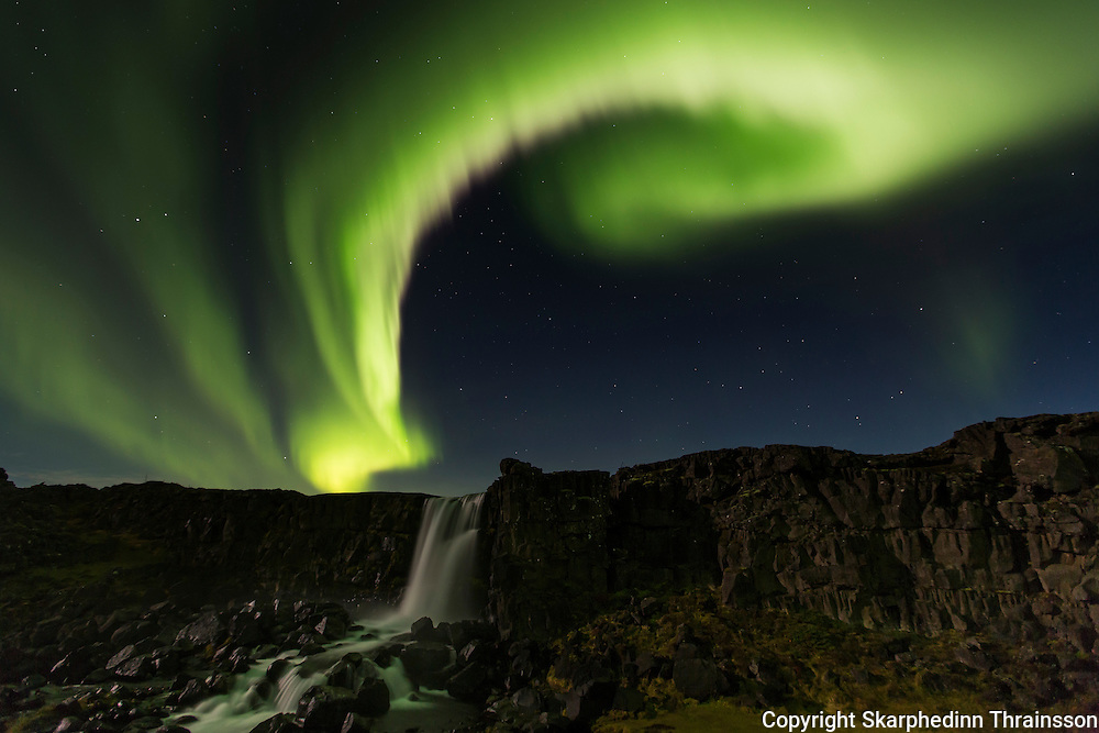 Aurora borealis over Öxarárfoss in Þingvellir National Park, southwest Iceland