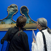 """MILAN, ITALY - SEPTEMBER 21:  Visitors admire """"A couple with their heads full of clouds"""", oil painting by Salvador Dali at the Exhibition preview at Palazzo Reale on September 21, 2010 in Milan, Italy. Dali is back in Milan with Il sogno si avvicina, an exhibition that takes place at Palazzo Reale  and that focus on the relationship between the great Spanish artist's visions and his favourite themes:  landscape, dream and desire."""