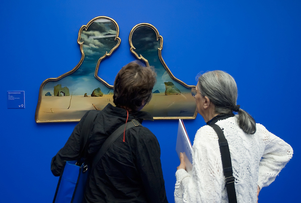 "MILAN, ITALY - SEPTEMBER 21:  Visitors admire ""A couple with their heads full of clouds"", oil painting by Salvador Dali at the Exhibition preview at Palazzo Reale on September 21, 2010 in Milan, Italy. Dali is back in Milan with Il sogno si avvicina, an exhibition that takes place at Palazzo Reale  and that focus on the relationship between the great Spanish artist's visions and his favourite themes:  landscape, dream and desire."