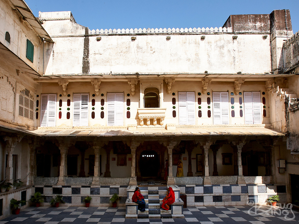 Women sit in the shade in a courtyard of the City Palace in Udaipur, Rajasthan, India <br /> <br /> Editorial & Non-Commercial use only