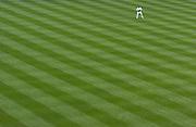 A lone fielder patrols a spacious outfield in Yankee Stadium..