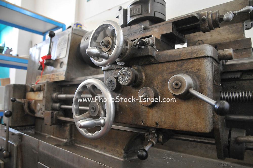 A lathe on a metal workshop floor