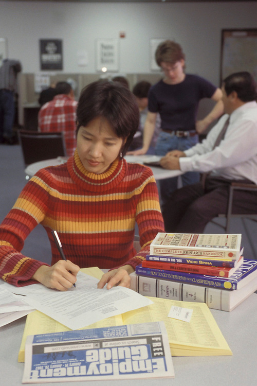 Asian-American female, 23, searches for entry-level position using State employment center resources and local newspaper.  Model Release.<br /> ©Bob Daemmrich/