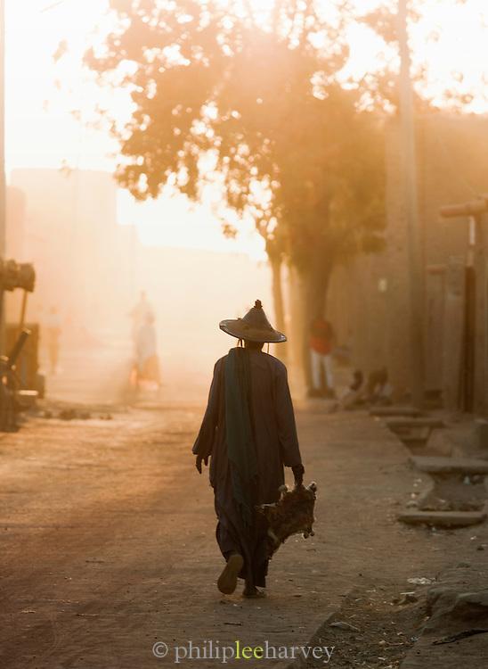 A man walks down a dusty street in Djenné, Mali