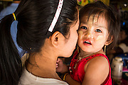 30 APRIL 2013 - MAHACHAI, SAMUT SAKHON, THAILAND:  A woman in a housing complex for Burmese migrants holds her daughter, who has thanaka powder on her face. The Thai fishing industry is heavily reliant on Burmese and Cambodian migrants. Burmese migrants crew many of the fishing boats that sail out of Samut Sakhon and staff many of the fish processing plants in Samut Sakhon, about 45 miles south of Bangkok. Migrants pay as much $700 (US) each to be smuggled from the Burmese border to Samut Sakhon for jobs that pay less than $5.00 (US) per day. There have also been reports that some Burmese workers are abused and held in slavery like conditions in the Thai fishing industry. Thanaka powder has been used by Burmese for over 2000 years for protection from the sun.          PHOTO BY JACK KURTZ