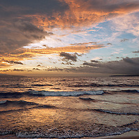 Clearing storm at dawn turns the ocean gold.