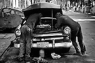 Two man repairing an old American car in the streets of Havana.