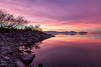 A calm morning over Utah Lake as the sky glows pink and purple.