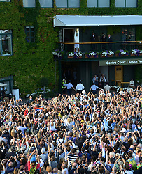 © Licensed to London News Pictures. 6th July 2014. London. UK. Djokovic shows winner's trophy to fans from balcony. Crowds and celebrities watch the The Men's Final between Roger Federer, SUI v Novak Djokovic, SER at the Wimbledon Tennis Championships 2014. Photo credit :  Mike King/LNP