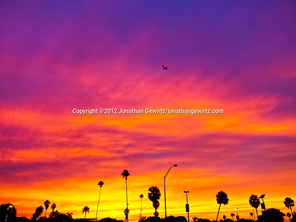 A brilliantly colorful sunset sky provides the backdrop as an aircraft passes high over palm trees and light posts at Hobie Beach in Miami, Florida. WATERMARKS WILL NOT APPEAR ON PRINTS OR LICENSED IMAGES.