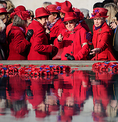 © Licensed to London News Pictures. 11/11/2016. London, UK. A group of elderly women, all dressed in red, places poppies in to the fountain during Silence in the Square, a service held in Trafalgar Square, London to mark Remembrance Day. A minutes silence is held on the 11th hour of the 11th day of the 11th month, to recall the end of hostilities of World War I.  Photo credit: Ben Cawthra/LNP