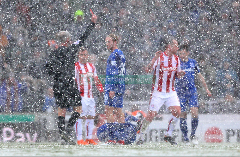 Stoke City's Charlie Adam (second from right) receives a red card from Referee Martin Atkinson (left) as heavy snow continues to fall at bet365 Stadium