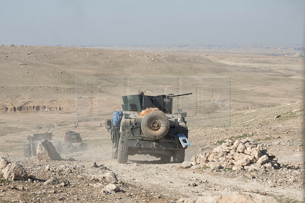 Licensed to London News Pictures. 20/02/2017. Albu Saif, Iraq. Armoured Humvees of the Iraqi Emergency Response Division drive into a valley as security forces prepare to carry out a flanking assault on the village of Albu Saif, Iraq.<br /> <br /> The settlement of Albu Saif is located on high ground overlooking Mosul Airport and as such is a strategic point that needs to be taken as part of the operation to retake the western side of Mosul. Photo credit: Matt Cetti-Roberts/LNP