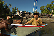 Local men push and help launch a new boat following the directions of its owner Abdul Hamed, 54 (first from right), in Lewoleba, Nubatukan subdistrict, Lembata district, East Nusa Tenggara province, Indonesia.