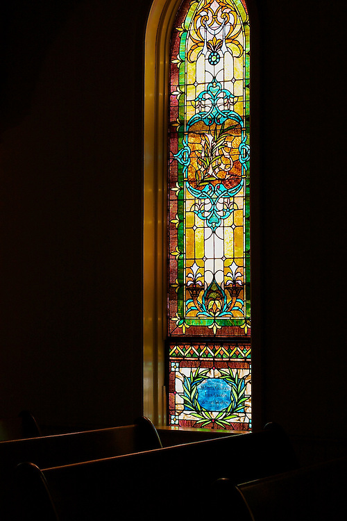 Stained glass window and wooden pews in a chapel.