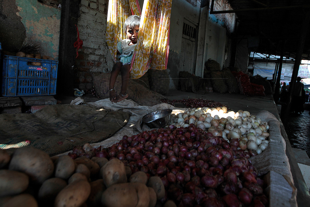 A young girl sits in a bag hanging from the ceiling above her fathers potato stand.  The slum of Cheetah Camp on the outskirts of Mumbai, India is a predominantly muslim community on living on the fringe while the city continues to grow.