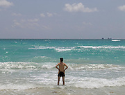 man standing knee deep in the water watching the surf Miami USA
