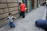 A street beggar has been noticed by a young Italian boy who points out the poor kneeling body to his parent. A stick lies on the ground with a paper cup to collect any spare change offered and a cash customer stands entering his pin number into the automated bank dispenser, his back to the underclass of society. This has become normal for what has become the modern face of Italian society in this once-grand medieval city. The city lies on the River Arno and is known for its history and its importance in the Middle Ages and in the Renaissance, especially for its art and architecture. A centre of medieval European trade and finance and one of the wealthiest cities of the time, Florence has been called the Athens of the Middle Ages.