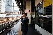 tokyo, Hamamatsucho - A man is checking his mobile phone and two shinkansen are passing on the left and refflecting on a glass on the right.