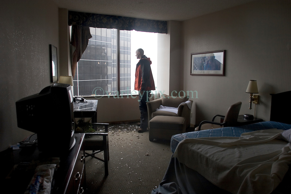 29 Aug 2005. New Orleans, Louisiana.<br /> Daily Mirror's Ryan Parry looks out of the shattered window of our room on the 25th floor of the Hyatt Hotel as the storm rages outside.<br /> Photo; Charlie Varley/varleypix.com