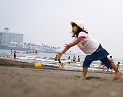 Girl playing ball on the beach at Kamakura, Tokyo, Japan. Taken as candid, with the camera sitting on a blanket, letting autofocus make the decision. Editorial Only..