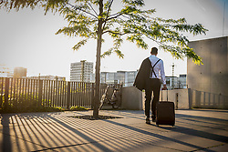 Rear view of a businessman pulling wheeled luggage at sunset, Munich, Bavaria, Germany