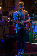 A fifteen year-old teenager sings and plays the guitar during a live gig in south London, UK.