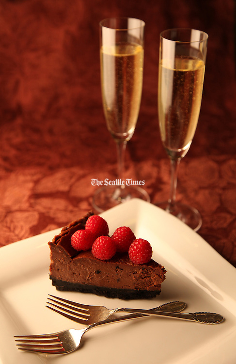 Chocolate cheesecake serves as a romantic Valentine's Day dessert for two. Here topped with fresh raspberries. (Genevieve Alvarez / The Seattle Times)