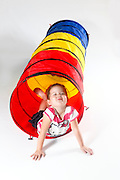 Indoor playground girl emerges from a tunnel On white Background