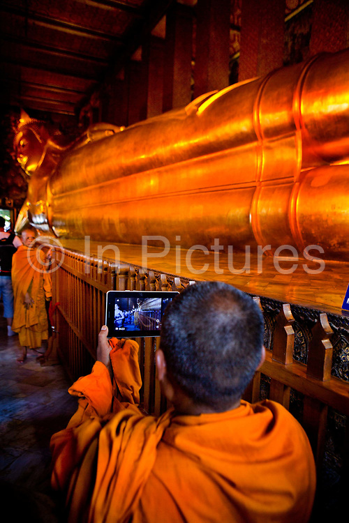 Monks using ipad or tablet computer to photograph the Reclining Buddha in Wat Pho temple, Bangkok. Wat Pho is one of the largest and oldest wats in Bangkok (with an area of 50 rai, 80,000 square metres), and is home to more than one thousand Buddha images, as well as one of the largest single Buddha images of 160ft length: the Reclining Buddha .