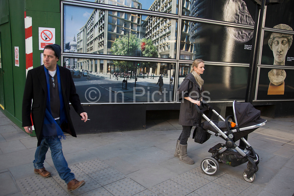 Large scale picture hoarding protecting a construction site in the City of London, UK. People walk past interracting with the picture, unawares.