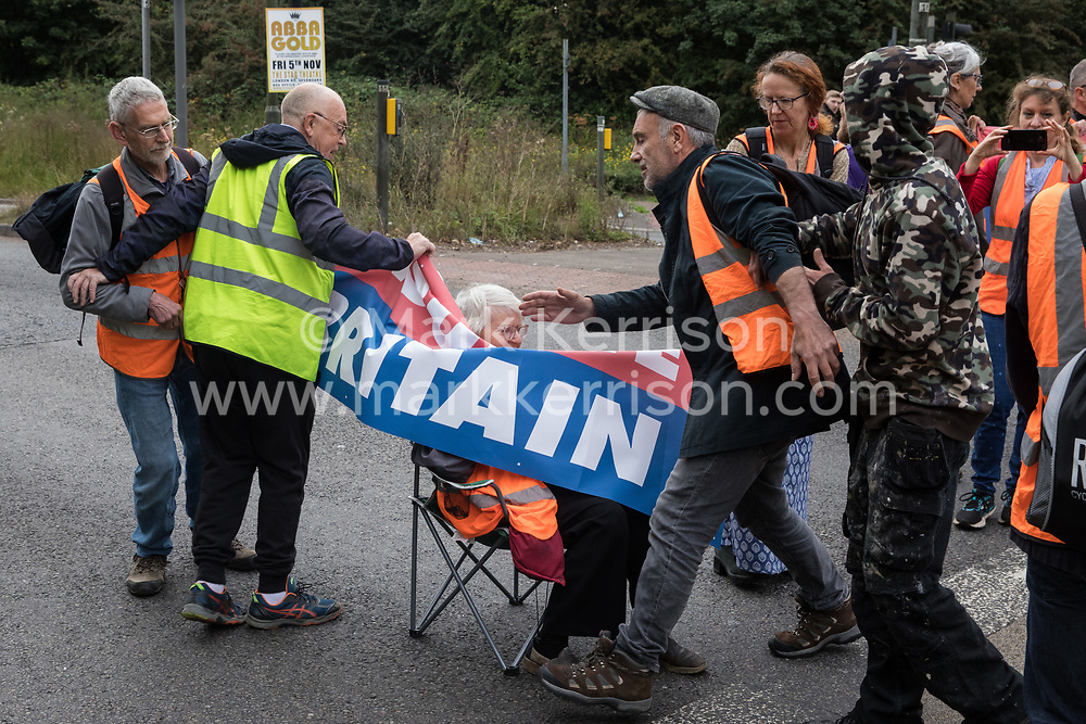 Godstone, UK. 13th September, 2021. Two men try to pull away a banner from Insulate Britain climate activists blocking a slip road from the M25, causing a long tailback on the motorway, as part of a new campaign intended to push the UK government to make significant legislative change to start lowering emissions. The activists, who wrote to Prime Minister Boris Johnson on 13th August, are demanding that the government immediately promises both to fully fund and ensure the insulation of all social housing in Britain by 2025 and to produce within four months a legally binding national plan to fully fund and ensure the full low-energy and low-carbon whole-house retrofit, with no externalised costs, of all homes in Britain by 2030 as part of a just transition to full decarbonisation of all parts of society and the economy.