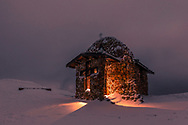 Small stone chapel in the mountain at winter night