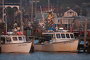 Newport, RI 2006 - Lobster boats at the state fishing peir with downtown Newport and a vibrant bouy tree on the peir in the background.