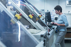 Female engineer working on computer in industry, Hanover, Lower Saxony, Germany