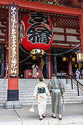 A Japanese couple dressed in kimono, bow before entering the main hall of the Sensoji Buddhist temple in Asakusa, Tokyo, Japan. The temple was built during the Kamakura period in 645 CE and is the oldest and most important temple in Tokyo.