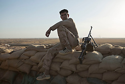 © Licensed to London News Pictures. 29/09/2015. Kirkuk, Iraq. A Kurdish peshmerga fighter rests on a sandbag wall at a front line near to Kirkuk, Iraq, the evening before an offensive to take 11 villages from the Islamic State.<br /> <br /> Supported by large amounts of coalition airstrikes, members of the Iraqi-Kurdish peshmerga today (29/09/2015) took part in an offensive to take seven villages across a large front near Kirkuk, Iraq. By mid afternoon the Kurds had reached most of their objectives, but suffered around 10 casualties all to improvised explosive devices. All seven villages were originally Kurdish and settled with other ethnic groups during the Iraqi Arabisation process of the 1970's and 80's. Photo credit: Matt Cetti-Roberts/LNP
