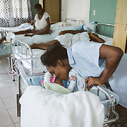 INDIVIDUAL(S) PHOTOGRAPHED: . LOCATION: St. Damien Hospital, Nos Petits Frères et Sœurs, Tabarre 41 Commune, Haïti. CAPTION: Fessiva Lamour bends down to kiss her daughter Jessica, who was born three days before at St. Damien Hospital.
