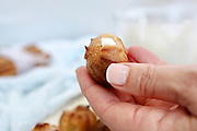 Freshly baked Cream Puffs (Eclairs) being filled with whipped cream.  This image has a restriction for licensing in Israel