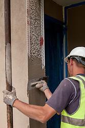 Plasterer working on refurbishing a house