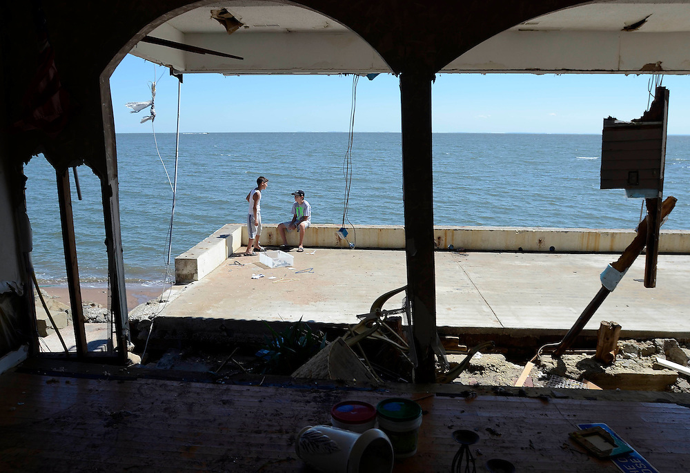 Adam Perrotti, left, talks with is friend, David Radziunas, at his father's home, Monday, Aug. 29, 2011, the day after it was severely damaged by Tropical Storm Irene, in East Haven, Conn. (AP Photo/Jessica Hill)