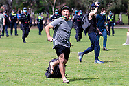 MELBOURNE, VIC - SEPTEMBER 19: A protestor holding a microphone and portable speaker is seen running from police during the Freedom protest on September 19, 2020 in Melbourne, Australia. Freedom protests are being held in Melbourne every Saturday and Sunday in response to the governments COVID-19 restrictions and continuing removal of liberties despite new cases being on the decline. Victoria recorded a further 21 new cases overnight along with 7 deaths. (Photo by Mikko Robles/Speed Media)